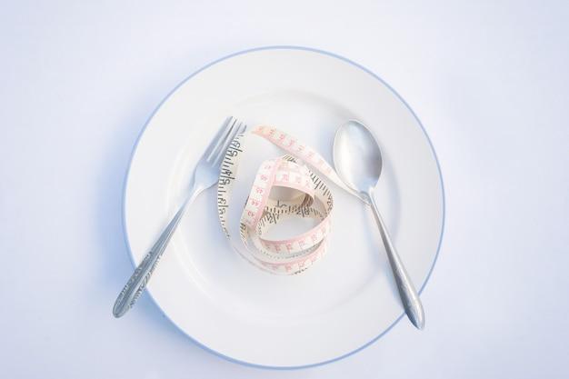 食事のレシピレシピ料理。スプーンとフォークで皿に黄色の測定テープ