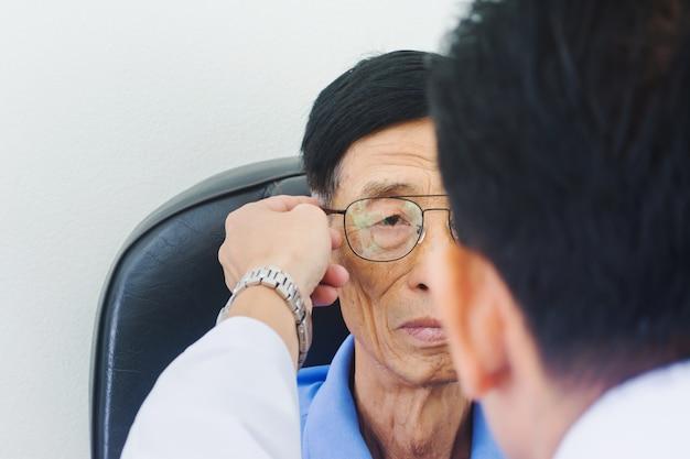 眼鏡技師の男性の手は彼の目をテストする老人に眼鏡をかける