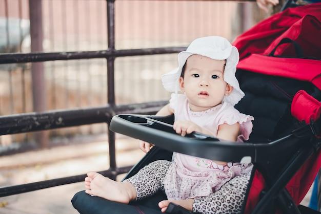 Маленький ребенок ребенок в шляпе, сидя в коляске на открытом зоопарке