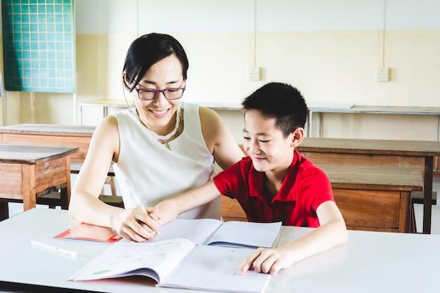 教室で宿題をする少年を教える先生