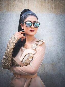 屋外スイミングプールのそばに立っている美しいアジアの女性の肖像画