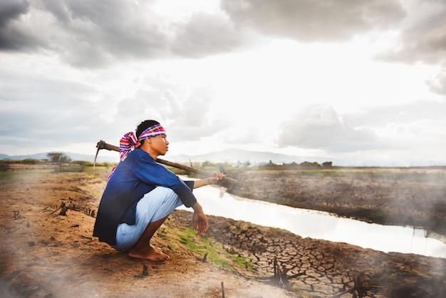 Безнадежный фермер сидит на сухой земле с мотыгой на плече и паром из земли. кризис глобального потепления, концепция экономического кризиса