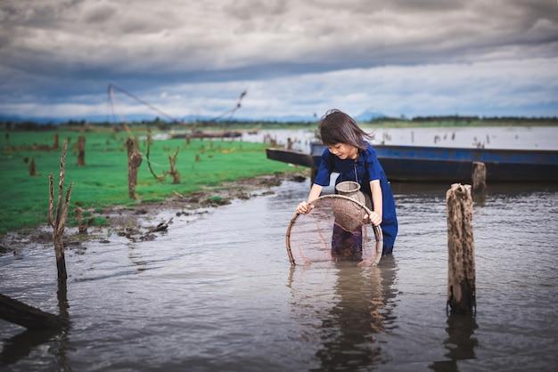 魚を捕まえて運河で楽しんでいる子供たち。タイの田舎の子供たちのライフスタイル。