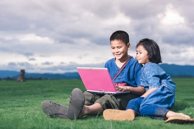 地元の衣装を着たアジアの子供たちは、タイの田舎で教育とコミュニケーションのためにラップトップを使用しています。