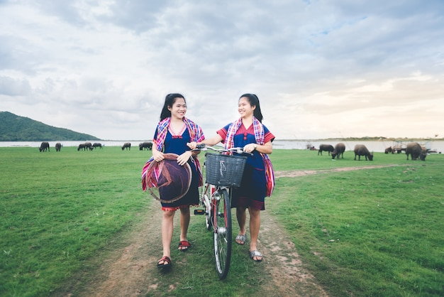 美しいアジアの女の子は自転車に乗ってタイの田舎で旅行を楽しむ