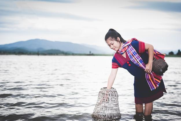魚のトラップで湖で釣り美しいアジアの女の子。タイの田舎の人々のライフスタイル