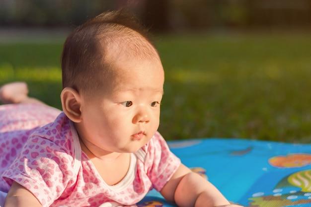 かわいいアジア人の赤ちゃんは、夕方に公園で地面に起こりやすい