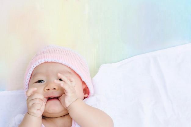 かわいいアジアの赤ちゃんは公園で地面に横たえます