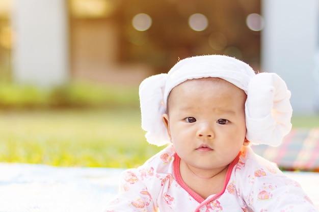 かわいいアジアの赤ちゃんの嘘は公園で地面に伏せやすい
