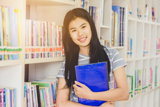本棚の前に立っている賢いアジアの学生の肖像