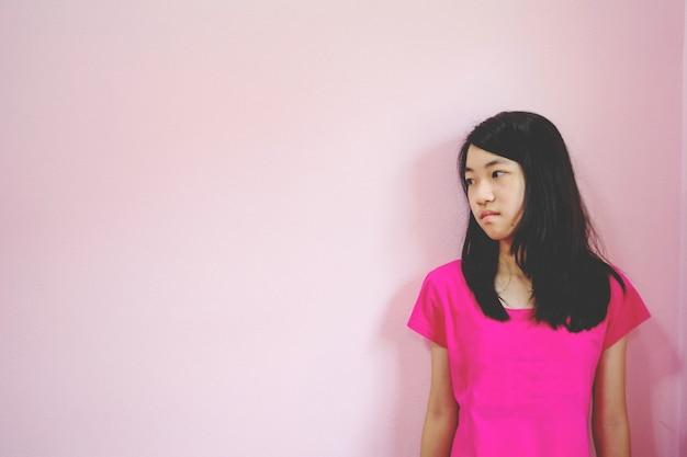 不景気の憂鬱な女の子はピンクの背景に立って見下ろす