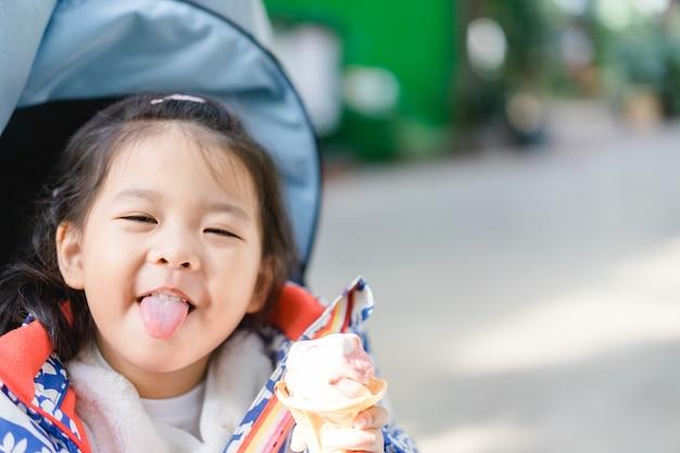 ハッピーリトルアジアの女の子、ソフトクリームやアイスクリームを食べる。北海道日本。