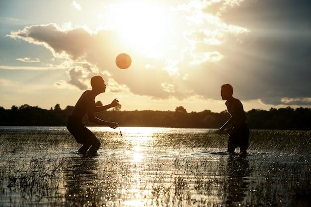 Пара мальчик играет в футбол с заходом солнца