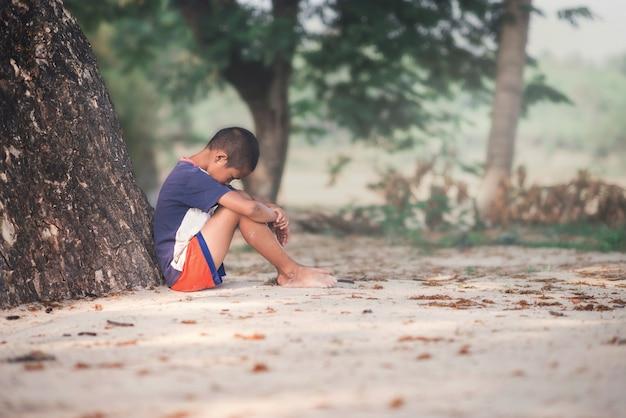 Грустный мальчик сидит с деревом