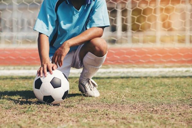 サッカーボールを持つ青チームコンセプトのサッカーフットボール選手