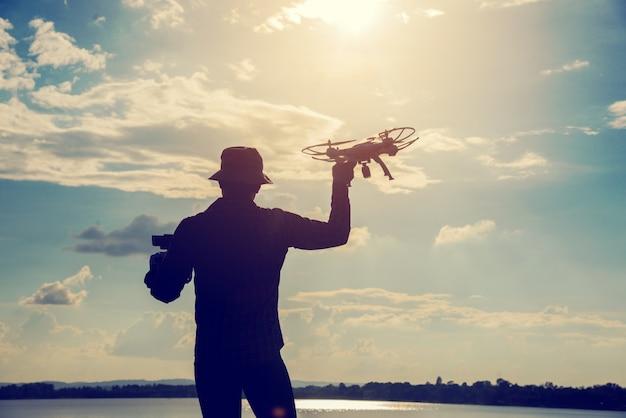 夕方に無人機で遊んでいる若い男のシルエット