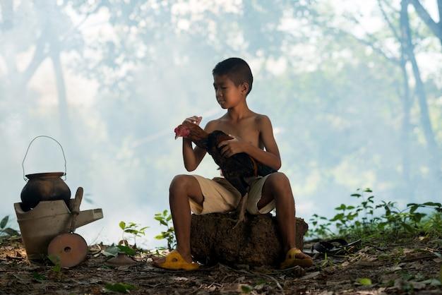 小さな笑顔の少年と田舎の緑の森の雄鶏