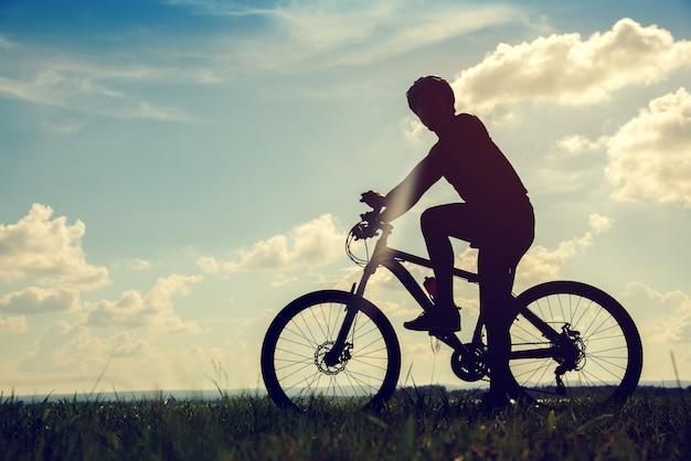 シルエットサンセットの背景にサイクリングの若い男