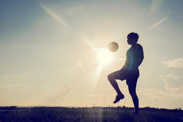 夕日の背景にサッカーボールを持つサッカー選手のシルエット。
