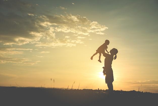 Силуэт счастливой молодой матери гармоничной семьи на открытом воздухе.