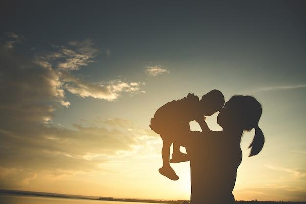 屋外で幸せな若い母親の母親のシルエット。