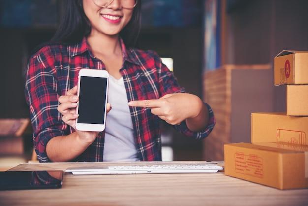 若いスタートアップの起業家の中小企業のオーナーは自宅で働いている
