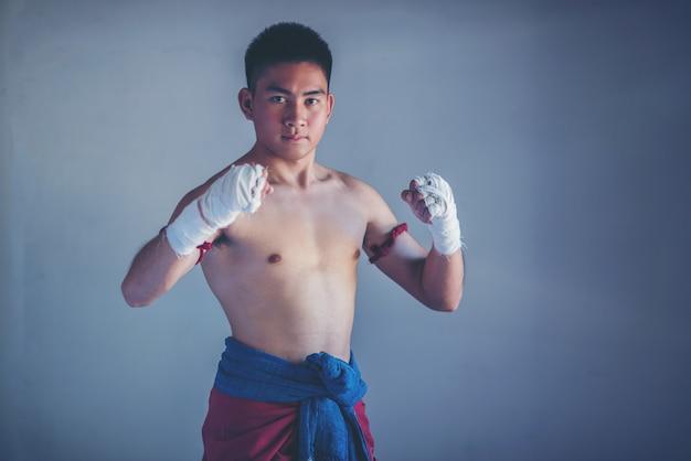 白いボクシング包帯とボクサーの男性の手のクローズアップ。