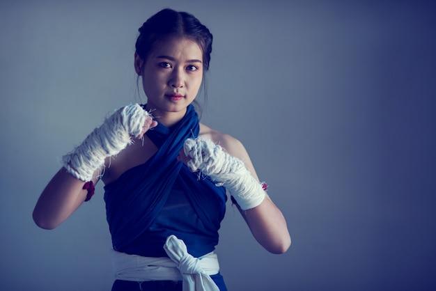 白いボクシング包帯とボクサーの女性の手のクローズアップ。