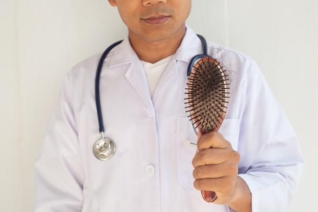 医者は脱毛を証明するためにヘアブラシを調べています。