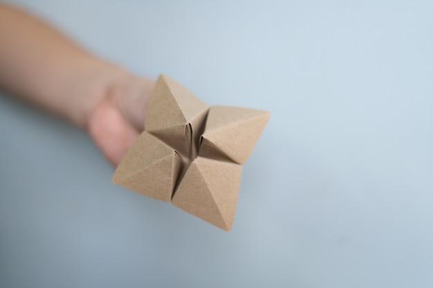 Женские руки держат бумажную гадалку на синем фоне