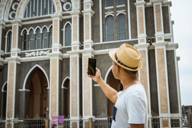 Туристы мужского пола используют мобильные телефоны, чтобы сфотографировать туристические достопримечательности