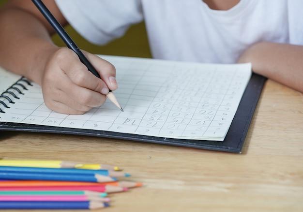 女の子の手は数学で宿題をしています。