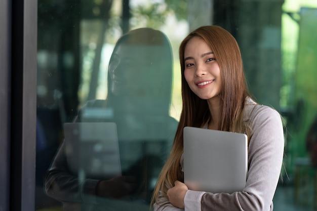 美しいビジネスの若い女性は彼女のオフィスの前で笑顔です。