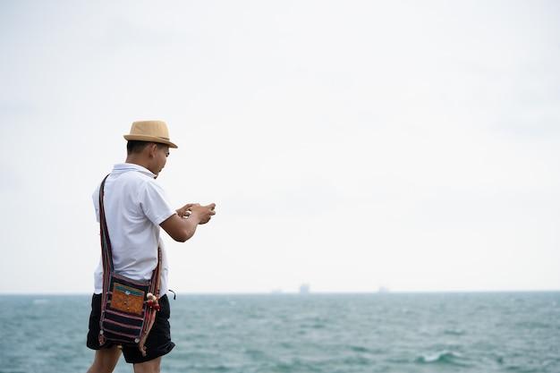 男性、観光客は携帯電話で海の写真を撮っています。