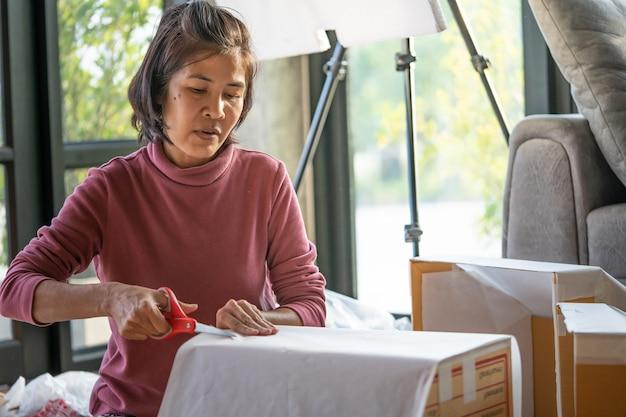 Женщина средних лет упаковывает продукты, чтобы доставлять их клиентам онлайн