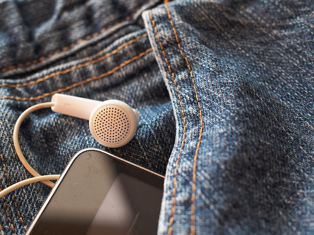 ポケットの古いジーンズのモバイルスマートフォンとイヤホン