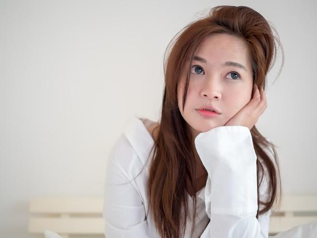 Симпатичная азиатская улыбка женщины и отдохнуть в постели после пробуждения в новое утро