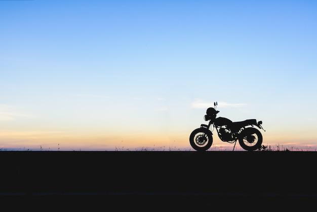 日没の背景とオートバイのシルエット