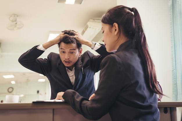 ストレスビジネスマンとの交渉中に頭を保持して手を持つビジネスマン、