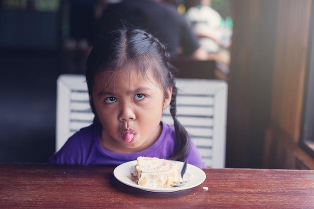 アジアの幸せな少女たちがアイスクリームを食べる