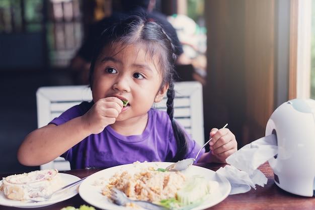 幸せなアジアの少女たちは、昼食、揚げた米、アイスクリームを机で食べる