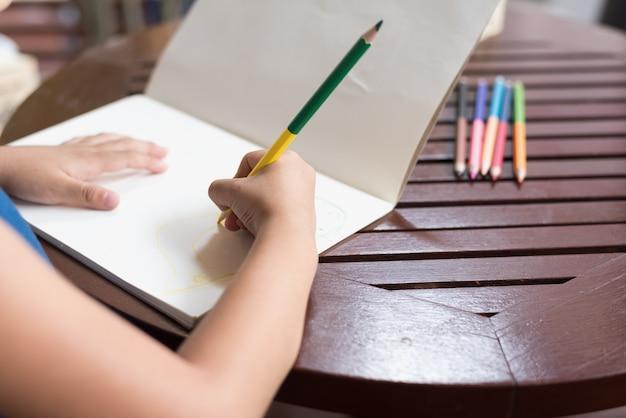 テーブル上にクレヨンで描く少女。