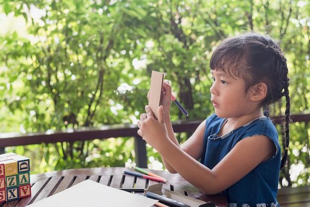 屋外でのプレー中の紙の上の少女の書き込み。