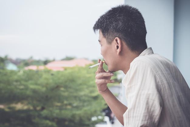 バルコニーベッドルームでのアジア人男性の喫煙。
