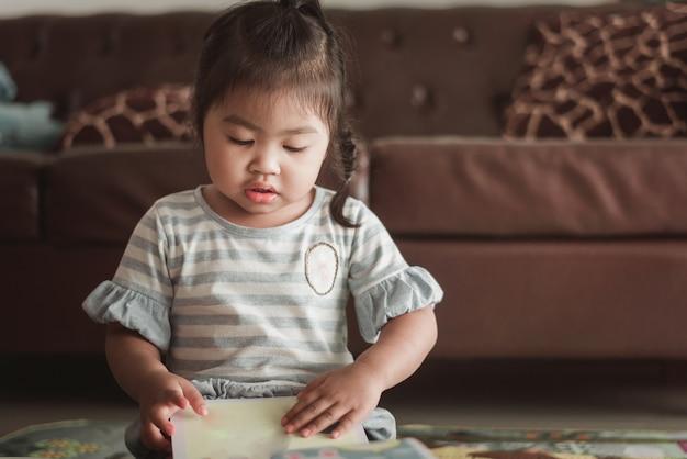 かわいいアジア人少女、カジュアルな服を着て本を読む