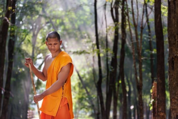 箒で働く仏教の修道士が寺院の落ち葉から芝生を掃除