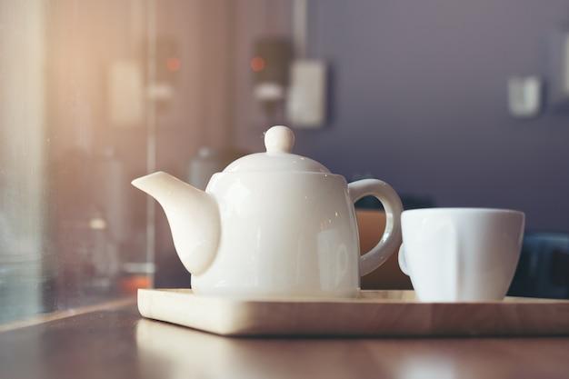 コーヒーショップでテーブルの上に紅茶と白い陶器のティーポットのカップ