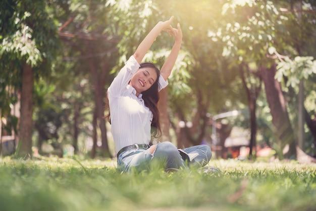 美しいアジアの若い女性は座って、フィールドでリラックス