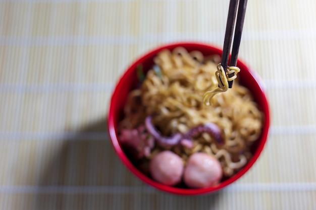 テーブルの上の黒いボウルに麺