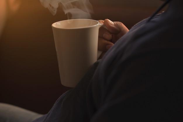 Люди держат кружку белого кофе